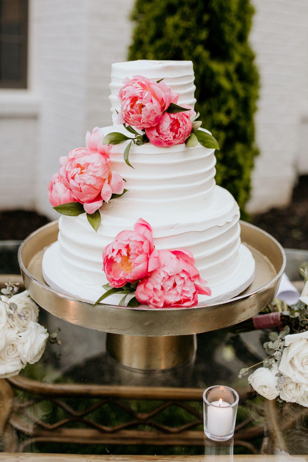 white wedding cake on gold stand