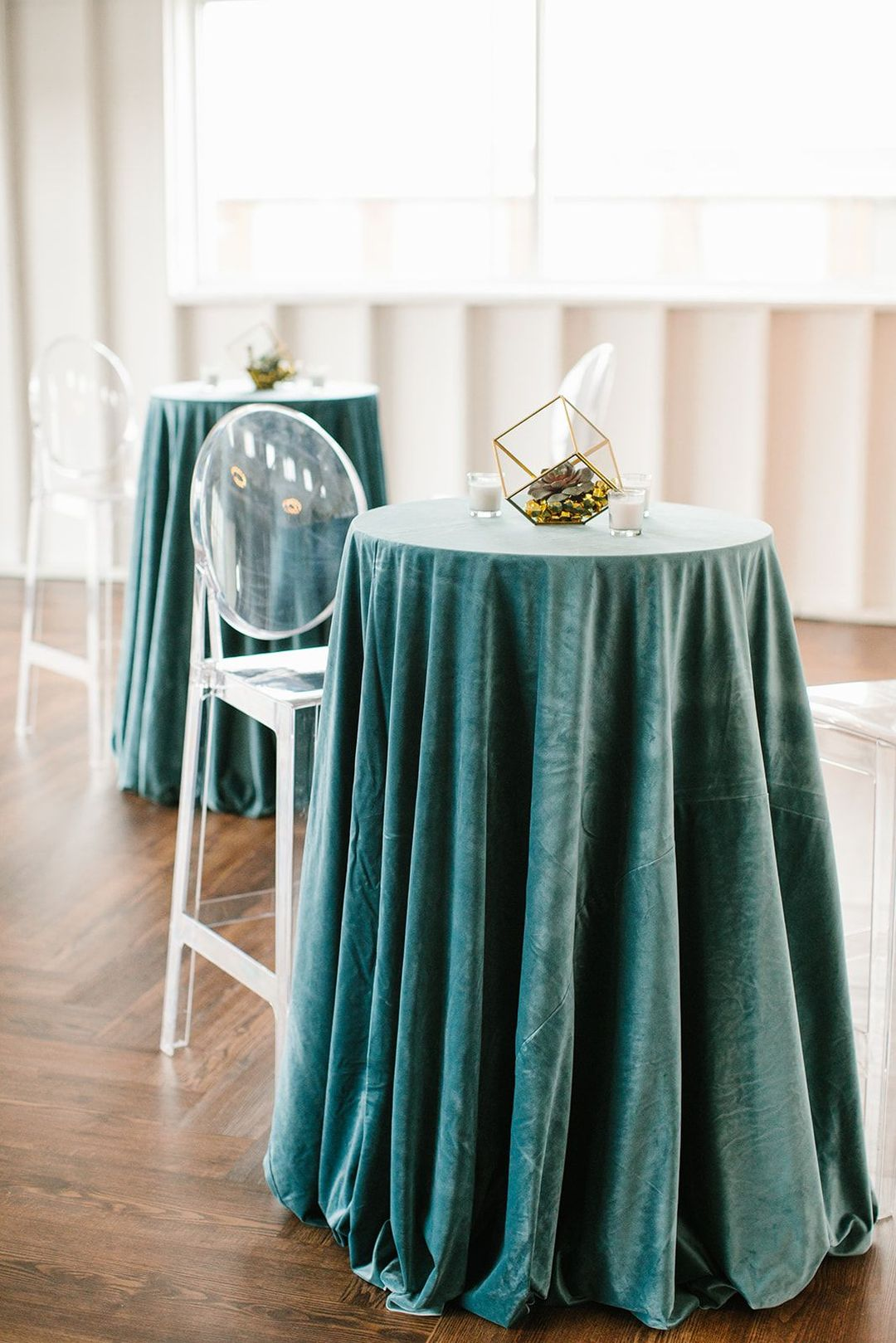 bistro table with blue linens, acrylic ghost barstool chairs